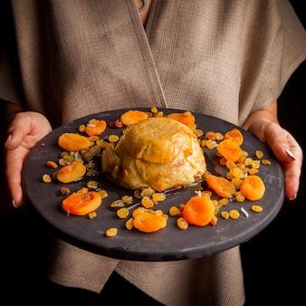 Shah pilaf con frutos secos y mano humana en plato redondo