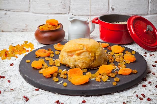 Shah pilaf con frutos secos y pan en plato redondo