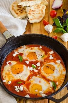 Shakshouka, plato de huevos escalfados en una salsa de tomates, chile, cebolla en la sartén.