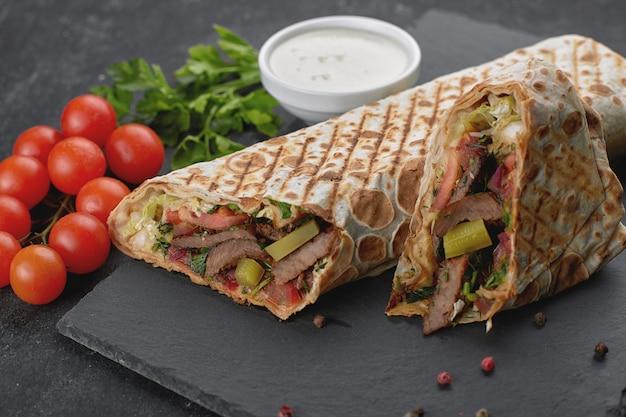 Shawarma de carne, cortado, con salsa, tomate, queso, hierbas y ajo, sobre pizarra negra