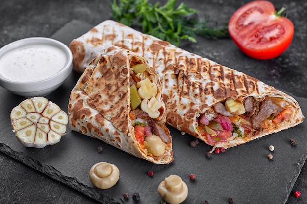 Shawarma con carne, con salsa, cebolla, pepinillos, tomate, ajo, hierbas y champiñones champiñones, en pizarra, sobre un fondo de hormigón oscuro