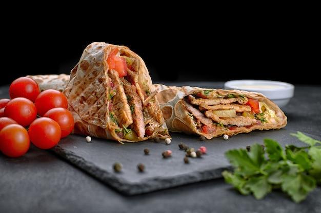 Shawarma de cerdo, sobre fondo negro, con hierbas, tomate y salsa