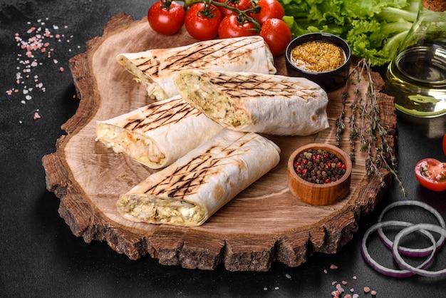 Shawarma fresco delicioso con carne y verduras en una mesa de hormigón oscuro. comida rápida, cocina turca