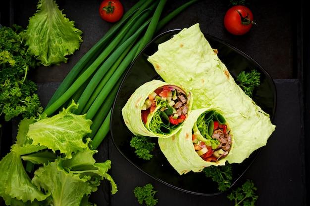 Shawarma de jugosa carne de res, lechuga, tomates, pepinos, pimentón y cebolla en pan de pita con espinacas. menú de la dieta