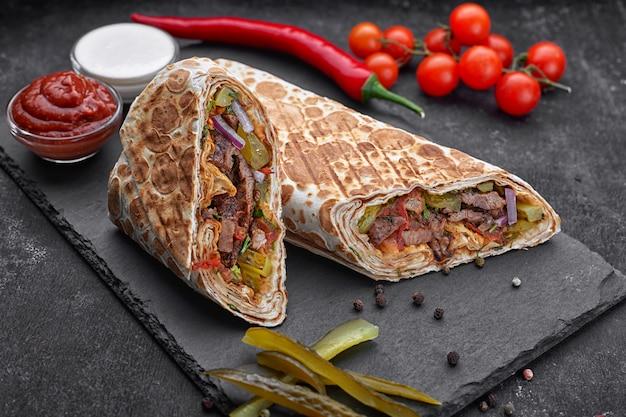 Shawarma con ternera, con salsa, cebolla, pepinillos, hierbas y pimiento rojo picante, sobre pizarra, sobre un fondo de hormigón oscuro