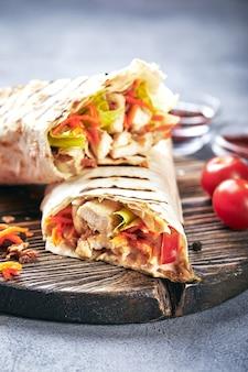 Shawarma tradicional oriental con pollo y verduras, doner kebab con salsas sobre tabla de cortar de madera. comida rápida. comida oriental.