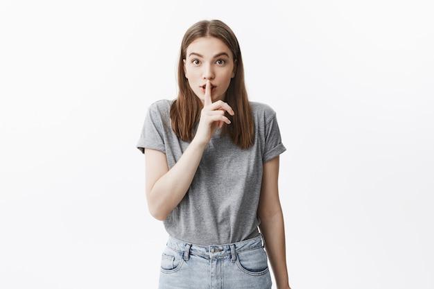 Shhh cerca de la atractiva joven morena alegre con cabello castaño y ojos marrones en ropa gris casual sosteniendo el dedo delante de la boca, con expresión amable, jugando con