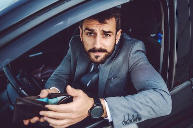 Shifty hombre de negocios caucásico sentado en su coche y tratando de sobornar al oficial de policía.