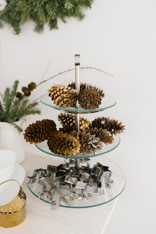 Shiggs de abeto y pino en una placa de vidrio y moldes de metal para galletas de navidad