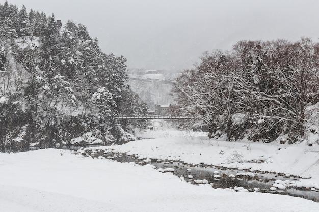 Shirakawago pueblo y puente de cuerda con nieve caída en temporada de invierno