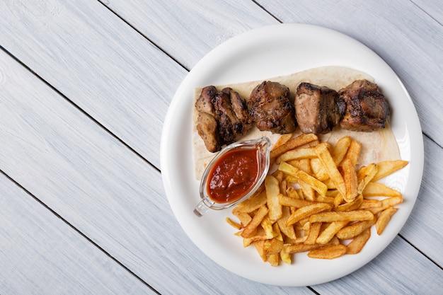 Shish kebab a la parrilla servido con papas fritas y salsa en la mesa de madera blanca