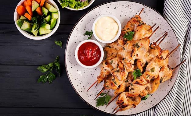 Shish kebab de pollo. shashlik - carne a la parrilla y verduras frescas. vista superior