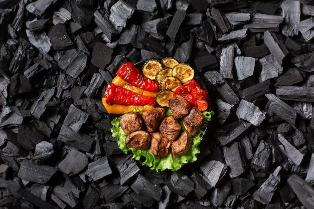Shish kebab y verduras asadas: pimiento, calabacín, cereza, tomate en un plato redondo
