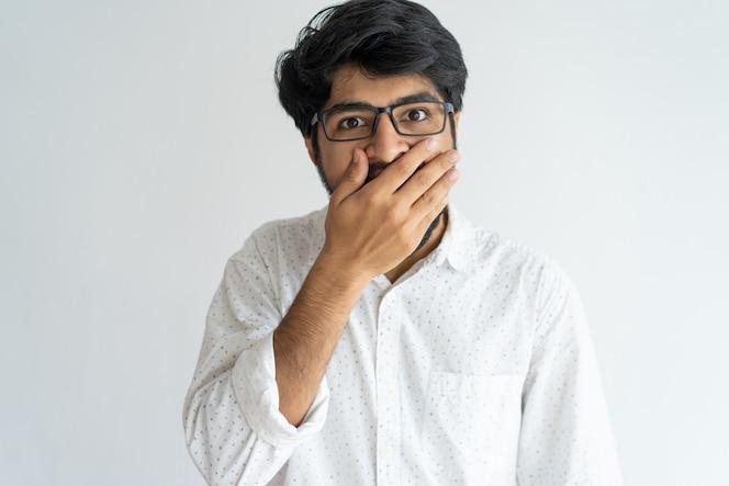 Shocked emocional indio hombre que cubre la boca en emoción.