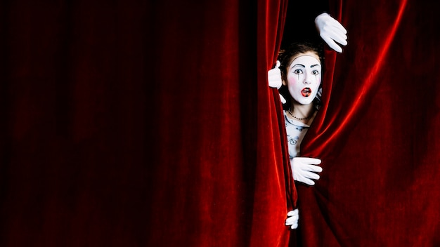Shocked female mime artist peeking de la cortina roja