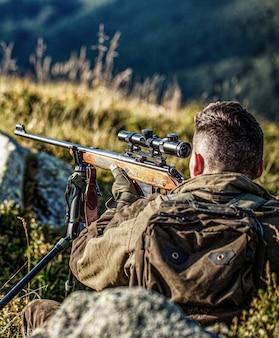 Shooter avistamiento en el objetivo el hombre está en la caza caza rifle de caza hombre cazador período de caza