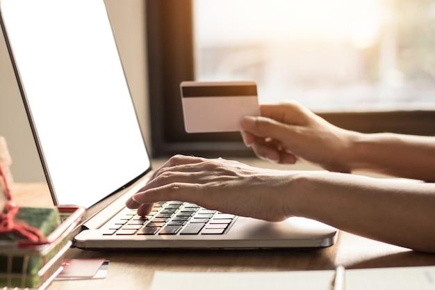 Shoping concepto en línea, casa de mujer o esposa usando laptop con tarjeta de cradit holding