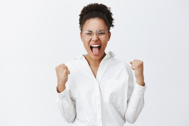 Sí chicas, lo hicimos. retrato de triunfante atractiva mujer africana con camisa blanca y gafas, levantando los puños cerrados y gritando de asombro y felicidad, celebrando la victoria sobre la pared gris