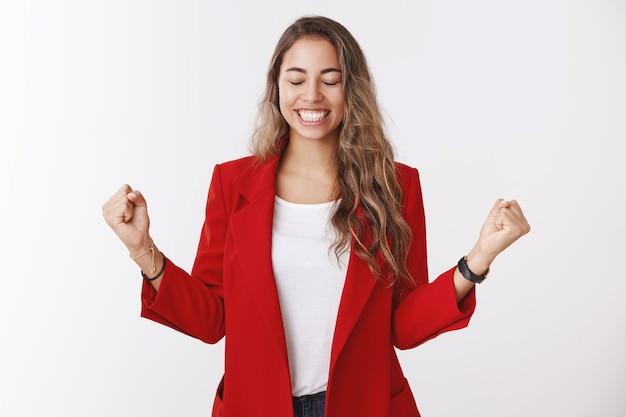 Sí, el éxito del sabor dulce gana. retrato de mujer empresaria guapa feliz aliviada emocionada celebrando la victoria de la buena suerte, apretando los puños hacia los lados cerrar los ojos sonriendo, regocijándose ganador