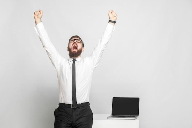 ¡sí! feliz, gritando, joven empresario barbudo con camisa blanca y corbata negra están de pie cerca de su lugar de trabajo y están triunfando con la boca abierta y los brazos levantados. aislado, tiro del estudio, fondo gris
