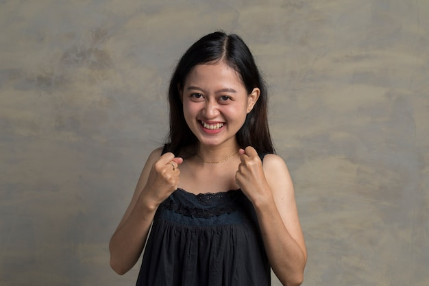 Si. feliz mujer asiática agitando los puños, haciendo gesto de ganador