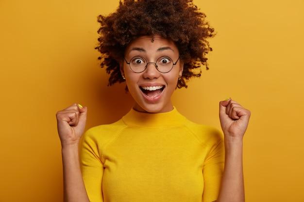 ¡sí lo hice! eufórica mujer de piel oscura levanta las manos con los puños cerrados, se ve feliz, vestida con ropa casual, se para contra la pared amarilla, se siente como ganadora. personas, emociones, estilo de vida.