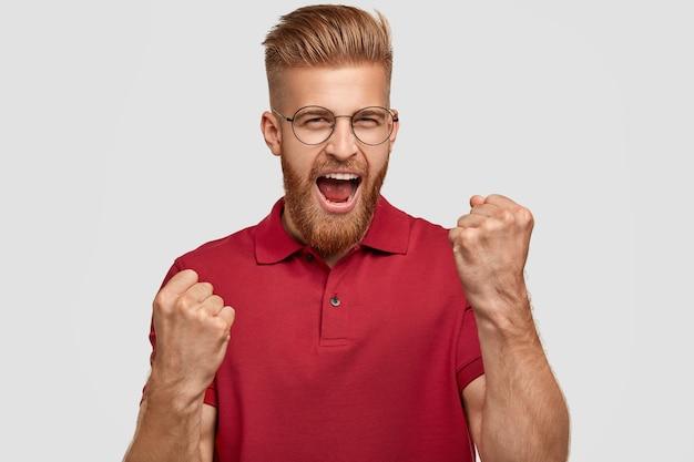 ¡sí, lo hice! hombre de jengibre feliz exitoso con corte de pelo de moda, aprieta los puños, tiene expresión de alegría