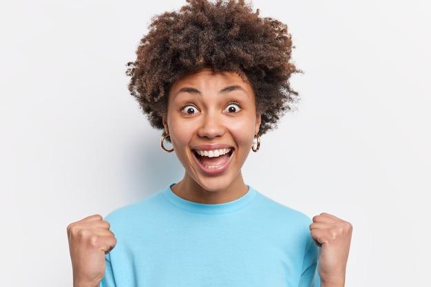 Sí lo hice. la joven afroamericana emocional llena de alegría aprieta los puños celebra el resultado exitoso mira con triunfo feliz de convertirse en campeón mira poses de juegos deportivos en interiores