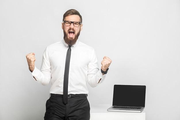 ¡sí! retrato de guapo feliz joven empresario barbudo con camisa blanca y corbata negra está de pie en la oficina está triunfando con la boca abierta. aislado, tiro del estudio, interior, fondo gris