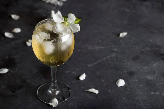 Sidra de manzana con cubitos de hielo y flor en copa de vino