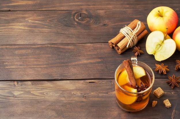 Sidra de vino caliente en tazas de vidrio con canela, anís y manzanas.