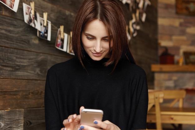 Siempre en contacto mujer joven atractiva moderna con fotos de edición de cabello chocolate usando aplicaciones en línea en el teléfono móvil, mirando la pantalla con una sonrisa feliz, mensajes