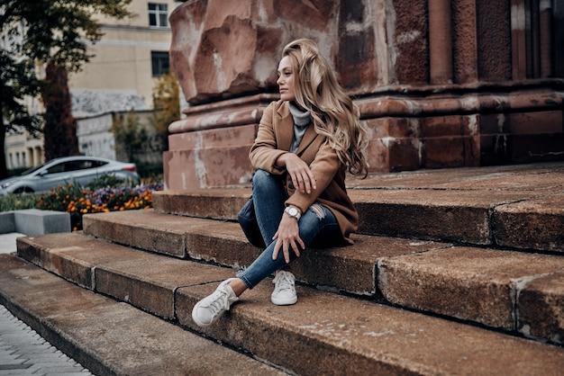 Siempre con estilo. hermosa joven mirando a otro lado mientras está sentado en las escaleras al aire libre