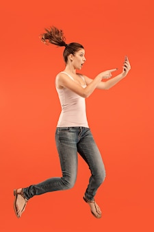Siempre en el móvil. longitud total de bastante joven tomando teléfono mientras salta contra el fondo rojo del estudio. móvil, movimiento, movimiento, conceptos de negocio