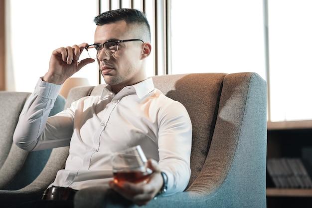 Siéntete descansado. joven empresario de pelo oscuro con gafas sintiéndose descansado mientras bebe whisky