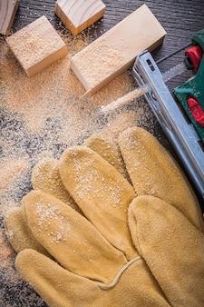 Sierra caladora eléctrica, serrín, guantes de cuero y tachuelas de madera.