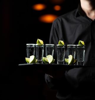 Siervo sosteniendo una bandeja de servicio con cócteles de limón.