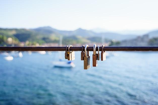 Siete cerraduras oxidadas en una baranda frente al mar en un día soleado