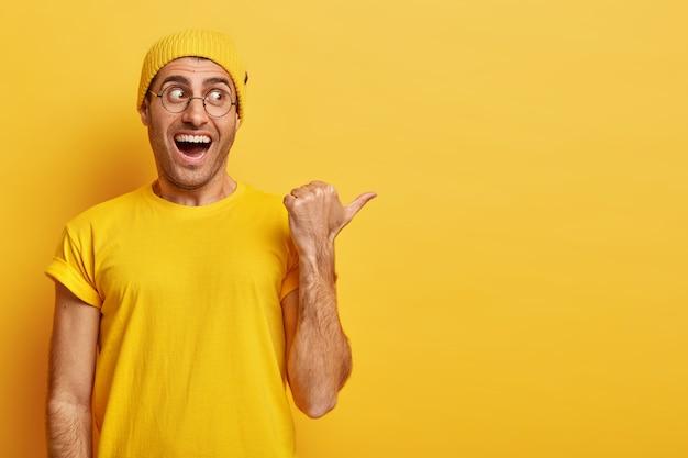 Siga este camino. hombre joven feliz con expresión de la cara llena de alegría, apunta con el pulgar hacia el lado derecho