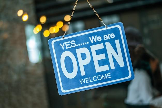Signo abierto a través del cristal de la ventana en la cafetería
