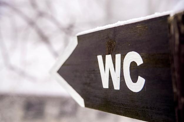 Signo de aseos públicos wc. signo y flecha del tocador. señal apuntando hacia el wc