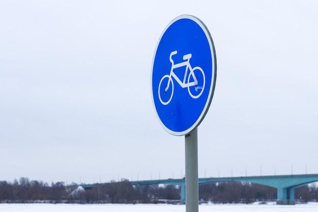 Signo de bicicleta en un círculo azul. signo de bicicleta en la nieve.