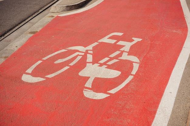 Signo de bicicleta sobre un fondo rojo en la calle