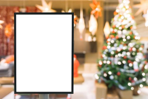 Signo en blanco con copia espacio para su mensaje de texto o simulacro de contenido en centro comercial moderno con árbol de navidad.