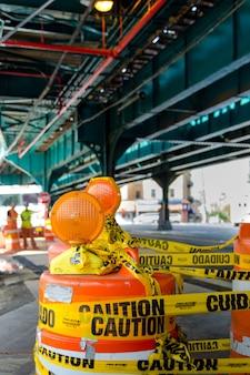 Signo de construcción en medio de la carretera debajo del puente del metro de nueva york