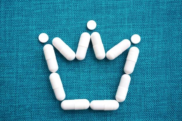 El signo de la corona se presenta en cápsulas blancas sobre un fondo azul. el concepto del tratamiento del peligroso coronavirus mortal. espacio libre