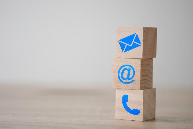 Signo de correo electrónico, dirección y pantalla de impresión de teléfono en cubo de bloque de madera para la página web de contacto de marketing comercial.