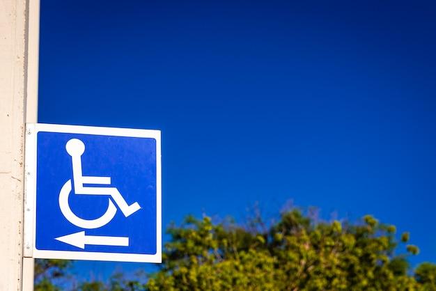 Signo cuadrado azul para indicar el camino a las personas con discapacidad en una silla de ruedas, copia espacio.