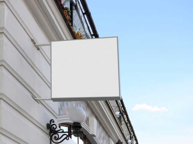 Signo cuadrado blanco en blanco en la pared, cielo