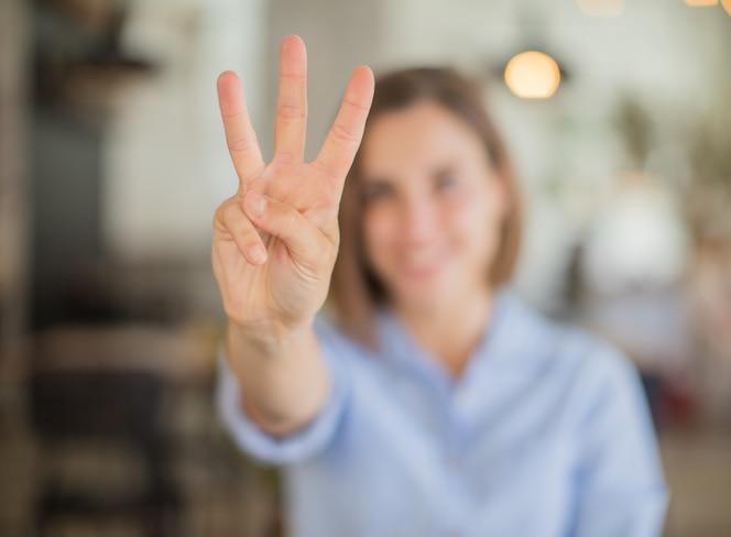 Signo de número de mujer joven contra fondo de empresa